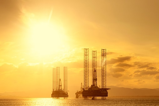 North Sea oil rigs moored in Cromarty Firth, Scotland, at sunset.